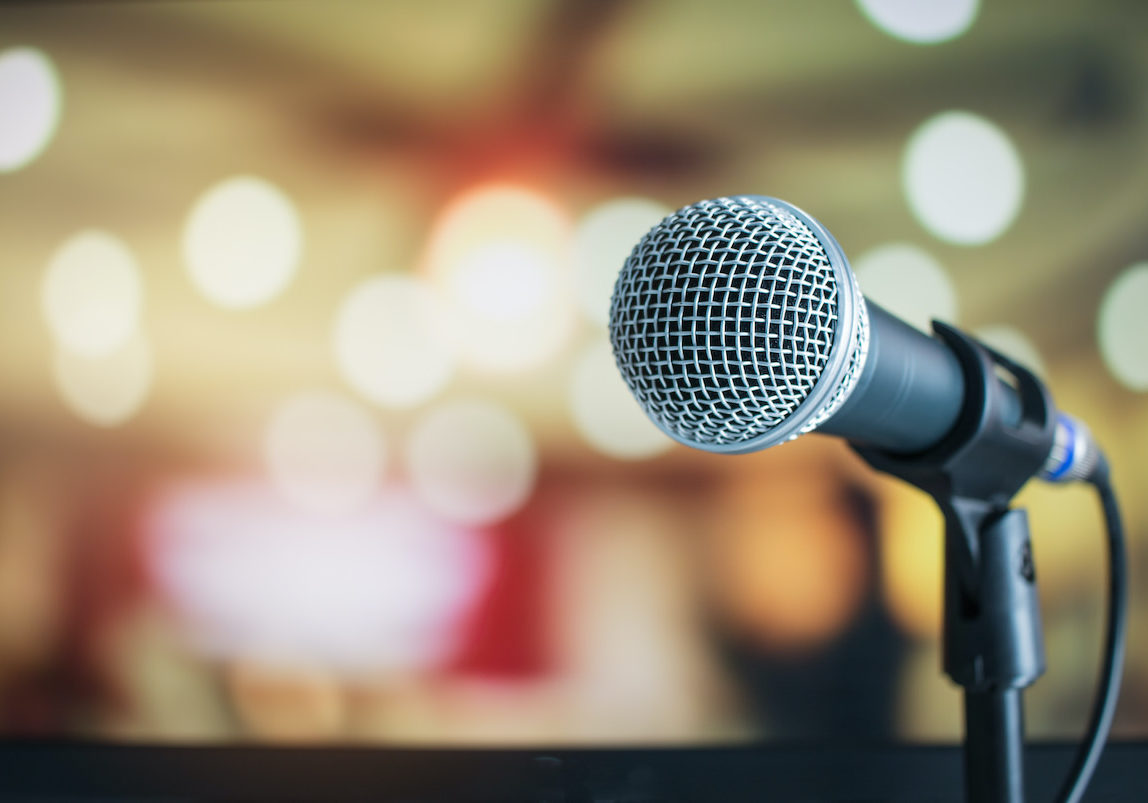 Microphone on abstract blurred of speech in seminar room or speaking conference hall light background
